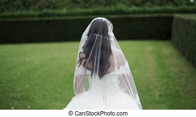 Bride in dress and veil walking in a park