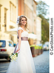 Bride in dress with violet bow and a bouquet of callas poses on the street