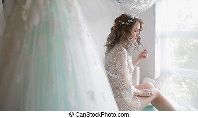 Bride in lace negligee near the window