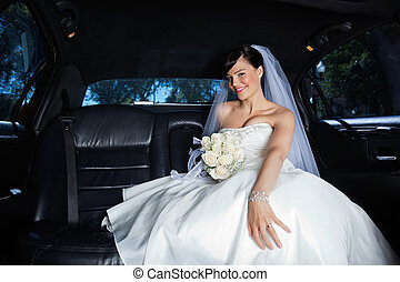 Bride in Limousine - Beautiful bride sitting in car holding...