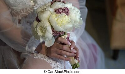 Bride in lingerie with bouquet sitting on chair