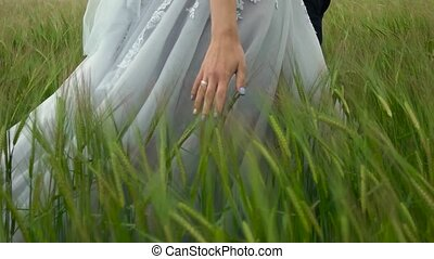 bride in suit walking ghrough the green field