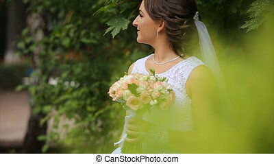 Bride in the wedding dress with bouquet in the park