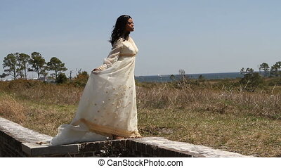 Black woman in a 1960's era bridal gown stands on a brick wall with the wind blowing across her dress.
