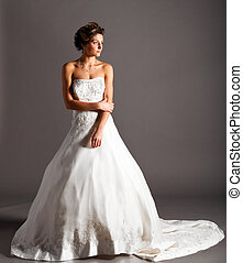 beautiful bride is standing in wedding dress on grey background