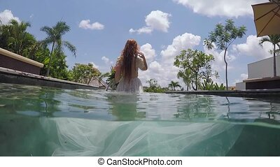 Bride in wedding dress comes to the pool