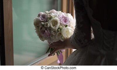 Bride in wedding dress near balcony with bouquet