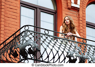 Bride in wedding dress on balcony of luxury apartment at the red hotel building