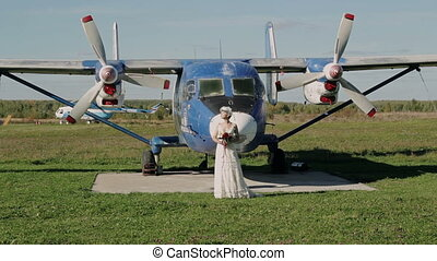 Bride in wedding dress stands near an old airplane