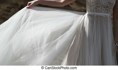 Bride in wedding dress waving cloth at wind