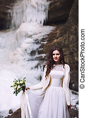 Bride in wedding dress with bouquet in front of glacier