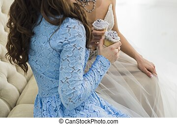 Bride in wedding dress with bridesmaid holding a beautiful blue cupcakes