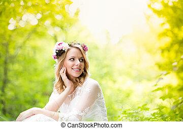 Bride in wedding dress with flower wreath, green nature.