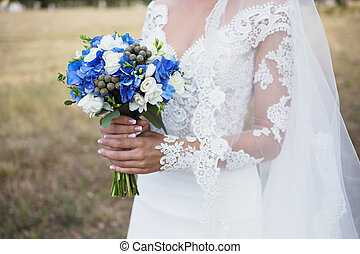 Bride in wedding dress with veil holding bouquet of blue and white flowers.