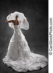 Bride in wedding luxury dress, back view, raised hands up. ...