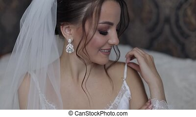 Bride in white boudoir dress, veil and in a silk robe. Wedding morning preparations before ceremony. Luxury bride with fashion hairstyle and makeup. Beautiful, lovely woman in night gown and veil