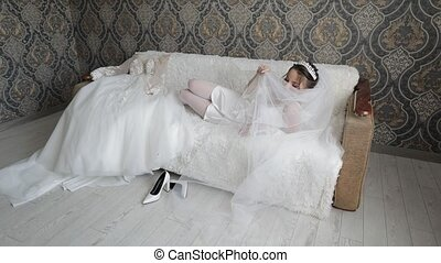 Bride in white boudoir dress, veil and in a silk robe. Wedding morning preparations before ceremony. Luxury bride with hairstyle and makeup. Beautiful, lovely woman on sofa in night gown and veil