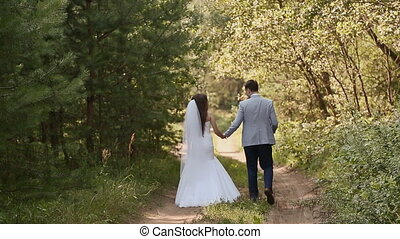 Bride in white dress and groom in the forest. They walk together holding hands. Happy together. Wedding day.