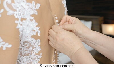 Bride in white dress is standing back to camera while bridesmaid is helping with fabric and clothing