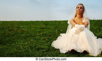 bride in white dress sits one on grass on hill slope close...