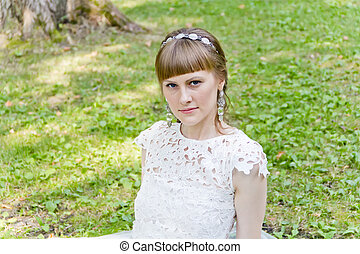 Bride in white dress sitting on the green grass - Beautiful ...