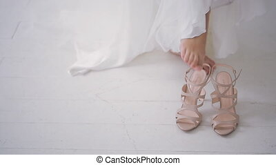 Bride in white dress wears beige shoes on wedding day on photo shoot