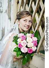 Bride in white dress with bunch of flowers