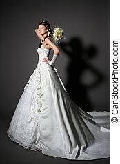 Bride in white elegance wedding dress with tail. Hand rised up with bouquet. Full length.
