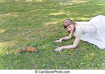 Bride in white lying on grass next to the squirrel - Bride ...