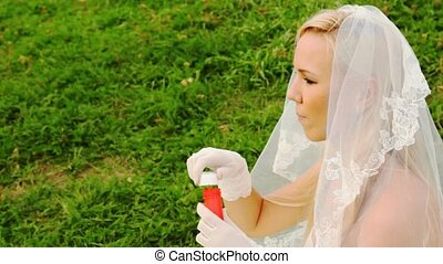 bride in white starts up soap bubbles on meadow