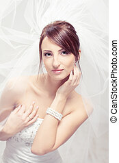 Bride in white veil looking at camera. Portrait. Fashion wedding shot.