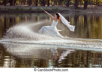 Bride is an athlete in a dress on surfing.