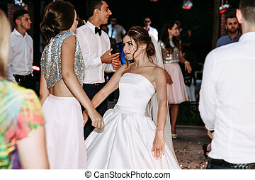 Bride is dancing with one of the bridesmaids