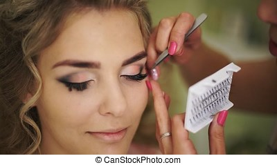 bride is glued with false eyelashes.Professional makeup for...