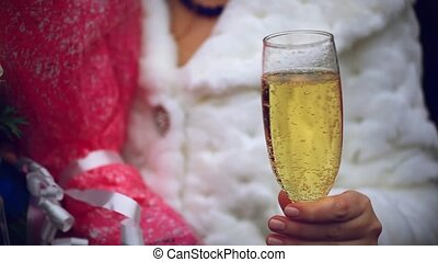 Bride is holding a glass of champagne and bouquet of flowers