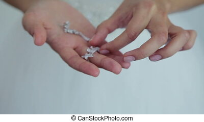 Bride is holding a silver earrings
