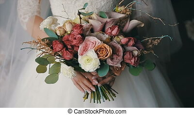 Bride is holding beautiful wedding bouquet of different...