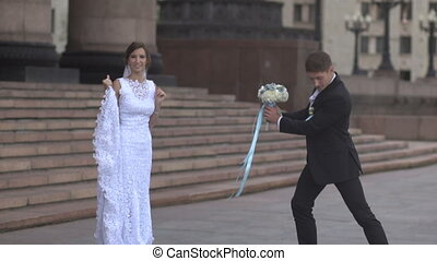 Bride jumping to the groom with a bouquet, barefoot