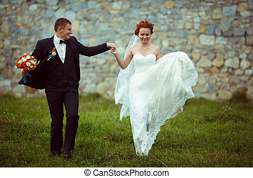 Bride jumps up holding groom's hand