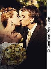 Bride kisses a groom tender closing her eyes