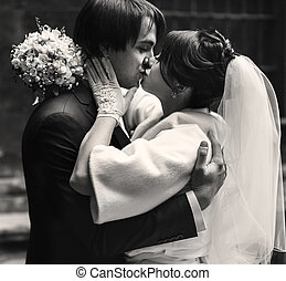 Bride kisses a groom while he hugs her tightly