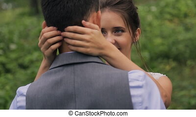 Bride kisses groom on wedding photosession in forest outdoors