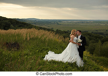 Bride kisses groom's face tenderly while they stand on a green hill