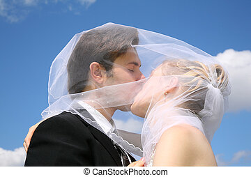 bride kisses with the fiance against the background of the sky
