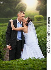 Bride kissing groom at garden