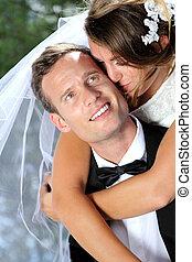 bride kissing her groom - portrait of beautiful bride...