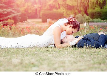 Bride kissing the lying groom on meadow