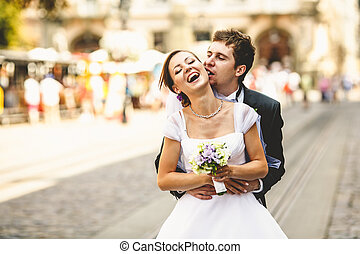 Bride laugh while a funny groom bites her ear
