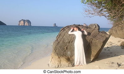 bride  leans on rock at beach against tropical islands