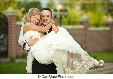 Bride leans to a groom while he holds her on his hands